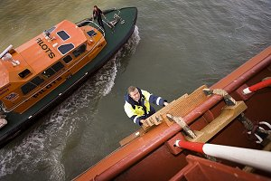 A pilot boards a ship in theThames Estuary