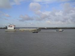 A commercial ferry passes a Thames fishing vessel