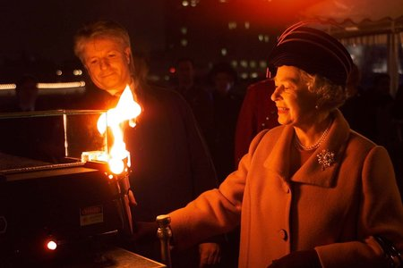 Queen Elizabeth II lights a beacon floating in the Thames as she travels by boat to the Millennium Dome at Greenwich. Earlier, she visited a shelter for homeless people and attended a service at Southwark Cathedral. (AP Photo by kind permission of the Pre
